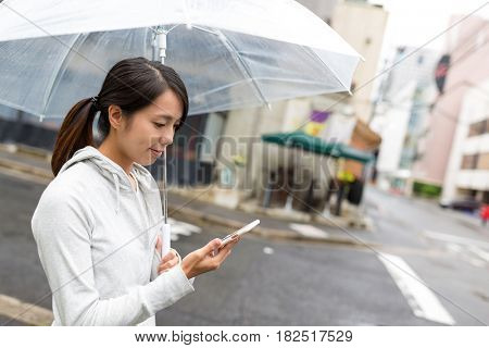 Woman holding umbrella and using mobile phone in Hiroshima city