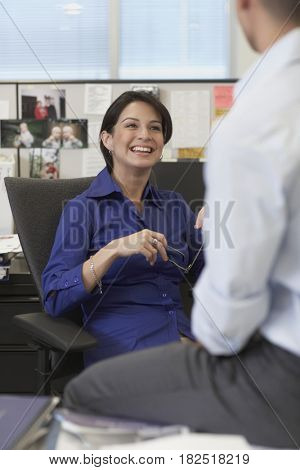 Hispanic businesswoman smiling at coworker