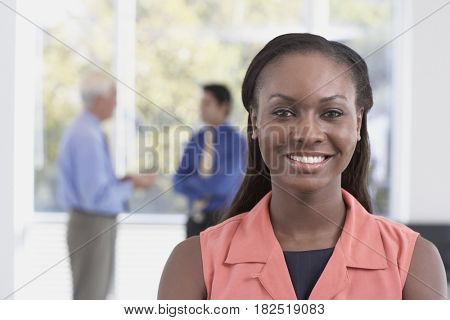 African businesswoman with co-workers in background