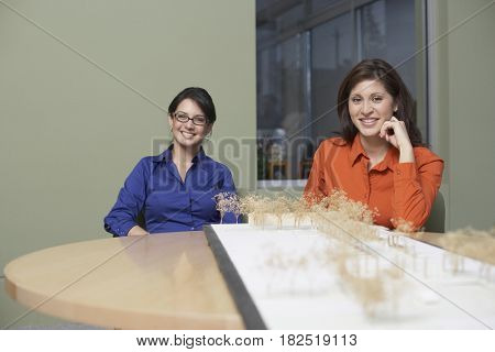 Portrait of Hispanic businesswomen with architectural model