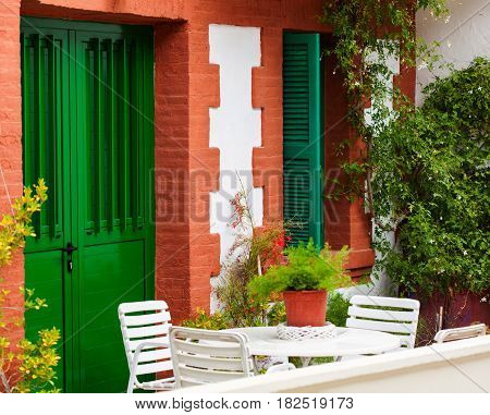 Small house with green doors and red walls. Chairs and coffee table in the yard.