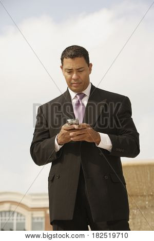 Hispanic businessman looking at cell phone