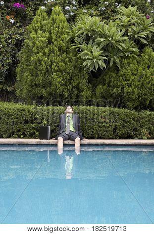 Hispanic businessman with feet in swimming pool