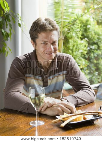 Middle-aged man sitting at table with glass of wine