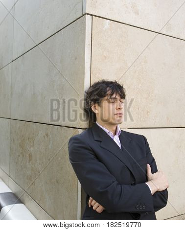 Hispanic businessman leaning on wall with eyes closed