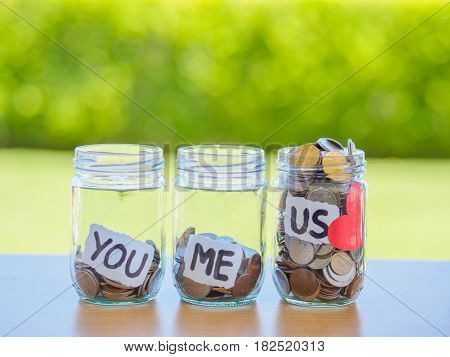 A lot coins in glass money jar on the wood table. Saving for family concept.