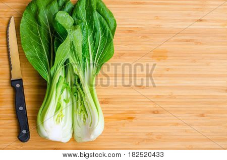 Bok choy with knife on wooden background. Pak choy is a type of Chinese cabbage(Qing geng cai )and one of the healthiest vegetable and popular superfood.