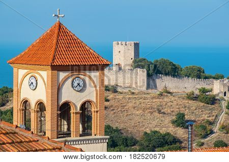 Bell Tower of the Church of Agios Eleftherios in Neos Panteleimonas village and medieval fortress of Platamonas at the distance. Pieria Macedonia Greece