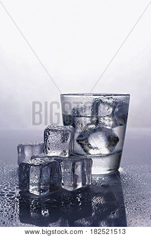 Shot Glass Of Alcoholic Drink As Tequila Or Vodka With Ice Cube