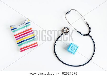 Pediatrics equipment with toys, stethoscope on white table background top view