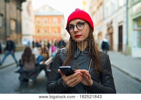 Beautiful woman with red lips and red hat uses smartphone and strolls along the medieval street