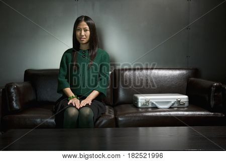 Asian businesswoman sitting on sofa