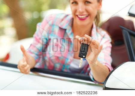Young pretty woman is standing near the convertible car with the keys in hand - concept of buying a used car or a rental car