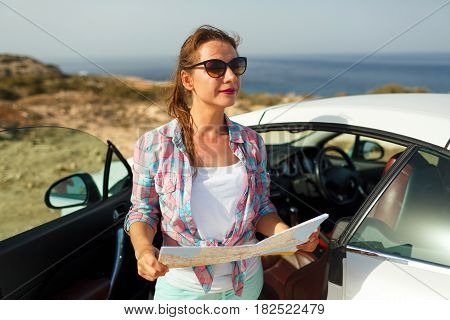 Young pretty woman see the map near the cabriolet - concept summer travel