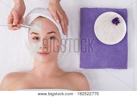 Face mask apply, spa beauty treatment, skincare. Woman getting facial care by beautician at spa salon, top view
