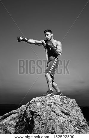 Vertical shot of a handsome young muscular boxer training outdoors on top of a rock confidence determination motivation energy lifestyle sportsman health body power effort endurance combat monochrome.