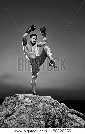 Black and white shot of a male fighter performing kickboxing outdoors training and working out exercising martial combat strengthen powerful energetic active athletics muscles torso abs body concept.