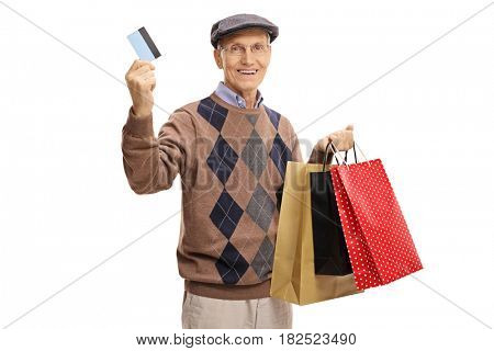 Mature man with a credit card and shopping bags isolated on white background