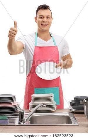 Young man with an apron showing a clean plate and making a thumb up gesture isolated on white background