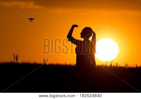 Silhouette Of Girl Looking At Drone