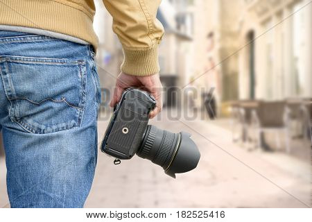 man photographer holding his photo camera outdoor