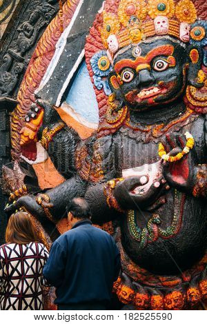 A man and woman place offerings at the foot of this depiction of Kala Bhairav in Durbar Square Kathmandu.