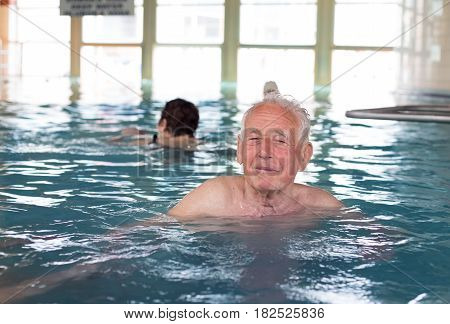 Senior man swimming in indoor pool and enjoying hydrotherapy