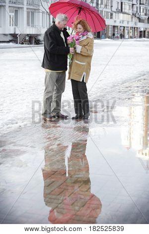 Happy senior couple with bouquet of flowers  standing under umbrella