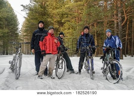 Tyumen, Russia - March 17, 2007: Group of cycle tourists stopped for rest in the wood on Taraskul lake route