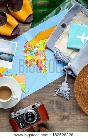 tourist lifestyle with photo camera and cup of coffee on wooden table background top view