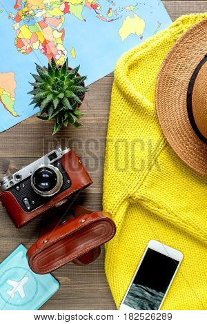 tourist lifestyle with photo camera and world map on wooden table background top view