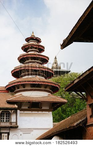 Round multi-tiered tower in Nasal Chowk with Taleju temple just visible in the background. Durbar Square Kathmandu.