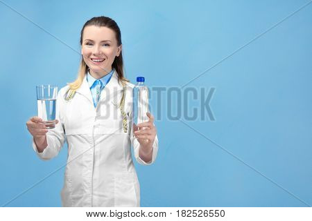 Young female nutritionist on light color background