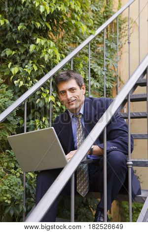 Businessman with laptop on stairs outdoors