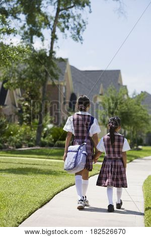 Asian sisters in school uniforms walking and holding hands