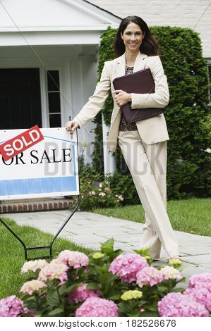 Hispanic female real estate agent and Sold sign in front of house