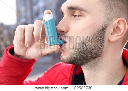 Young man using asthma inhaler on street