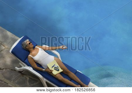 Senior Hispanic woman in lounge chair next to swimming pool