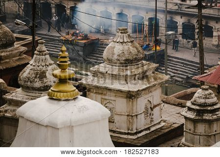 Smoke rises from bodies being cremated on funeral pyres in Pashupatinath temple. Kathmandu Nepal.