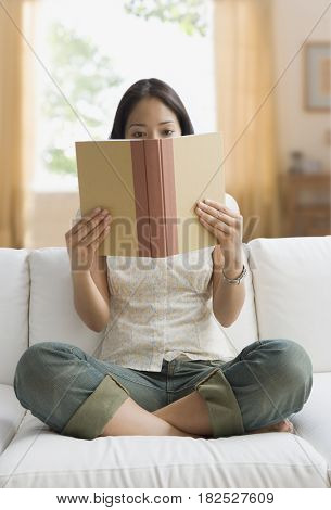 Pacific Islander woman reading on sofa