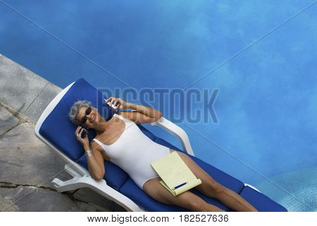 Senior Hispanic woman using cell phone next to swimming pool