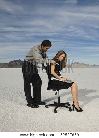 Hispanic businesspeople looking at laptop
