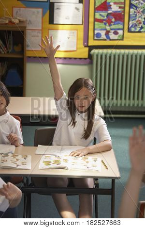 Asian girl with hand raised in class