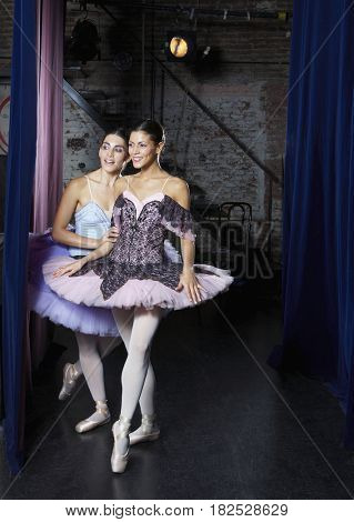 Hispanic female ballet dancers behind stage curtain