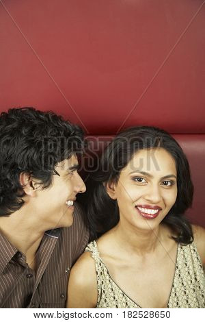 Hispanic man smiling at girlfriend