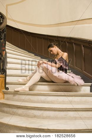 Hispanic ballerina sitting on stairs