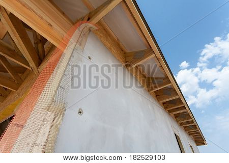 Corner of house with eaves, wooden beams and roof asphalt shingles
