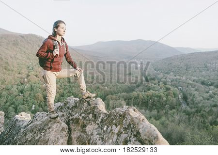 Traveler explorer girl with backpack standing on peak of cliff in the mountains and looking into the distance in summer