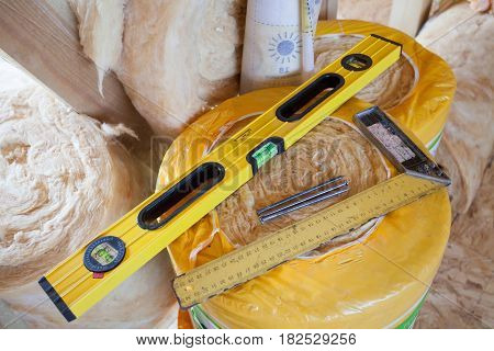 Construction level with square triangle on fiberglass insulation material