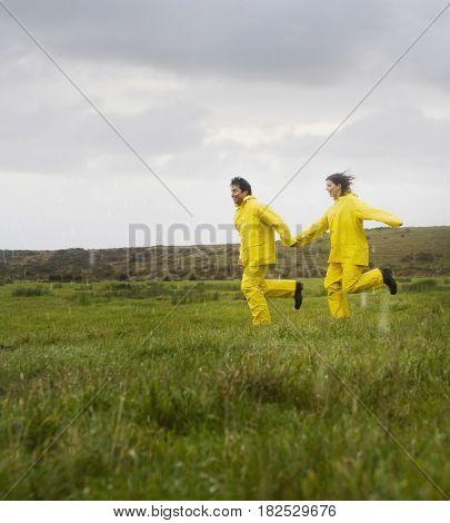 Hispanic couple in rain gear running